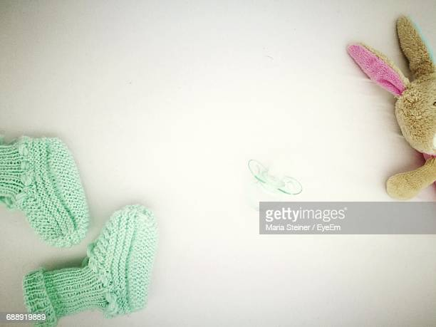 Knitted Socks And Pacifier By Stuffed Toy On Table
