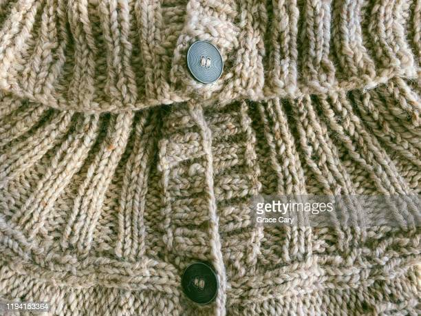 knitted sweater detail - button sewing item stock pictures, royalty-free photos & images