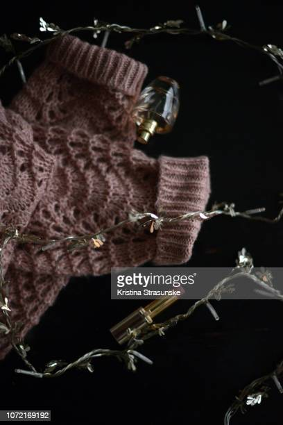 knitted sweater, ornament with lights, lipstick and perfume bottle - tricoté photos et images de collection