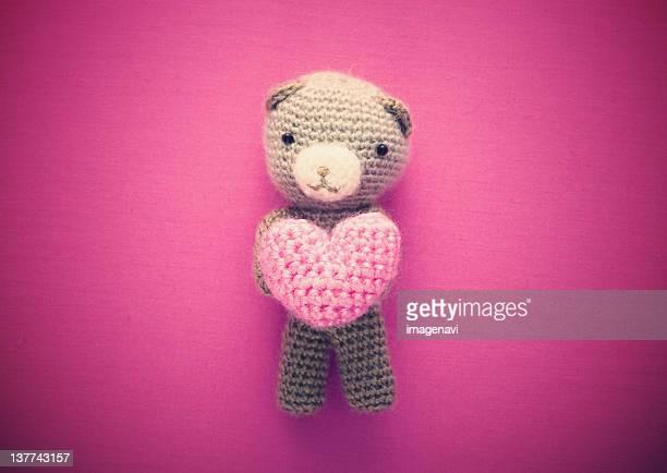 Knitted teddy bear holding heart
