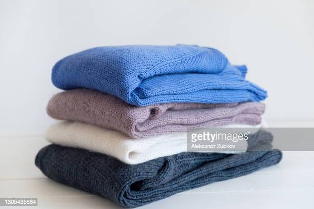 knitted woolen things of different colors, stacked in a pile, lie on a white wooden table. winter and autumn warm cozy sweaters for charity. the concept of storage, care and washing of handmade products. - jersey top fotografías e imágenes de stock