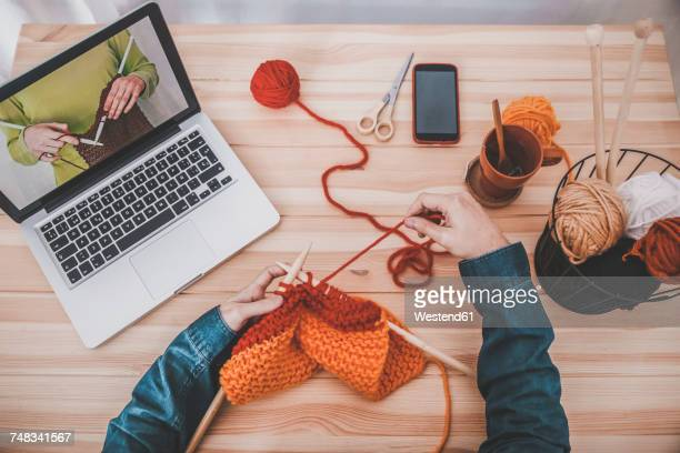 knitting man using laptop for watching online tutorial, partial view - tutorial stock pictures, royalty-free photos & images