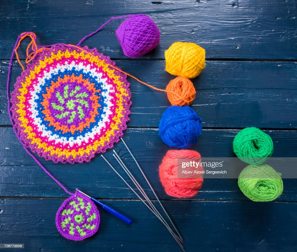 Knitting needles and multicolor yarn on blue table : Stock Photo