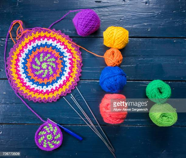 Knitting needles and multicolor yarn on blue table