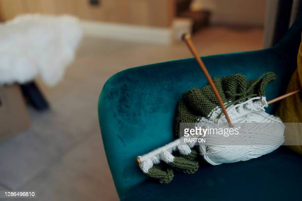 knitting needles and wool on arm chair - needlecraft stock pictures, royalty-free photos & images