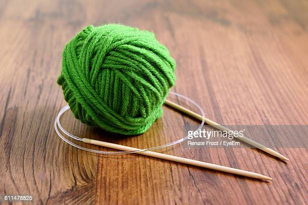 Knitting Needles With Ball Of Green Wool On Table