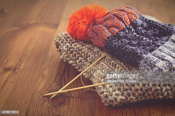 Knitting Needles With Hat And Scarf On Wooden Table