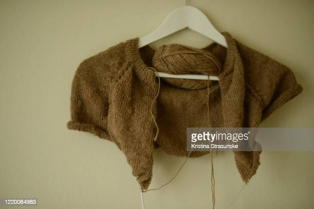 knitting sweater in brown color, work in progress, seen on a coathanger - incomplete stock pictures, royalty-free photos & images