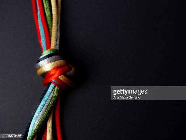 a knot with many twine of different colors on a black background - lace fastener stock pictures, royalty-free photos & images