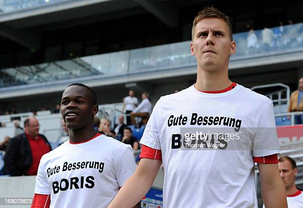 Knowldge Musona and his team mate Torsten Oerl of Augsburg enter the pitch with a shirt for Boris Vukcevic prior to the Bundesliga match between TSG...
