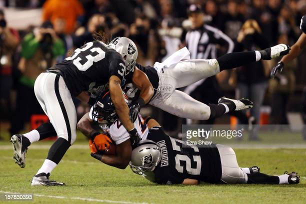 Knowshon Moreno of the Denver Broncos gets tackled by Tyvon Branch Matt Giordano and Philip Wheeler of the Oakland Raiders at OaklandAlameda County...