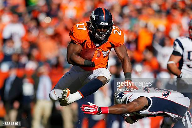 Knowshon Moreno of the Denver Broncos jumps over Duron Harmon of the New England Patriots in the second quarter during the AFC Championship game at...