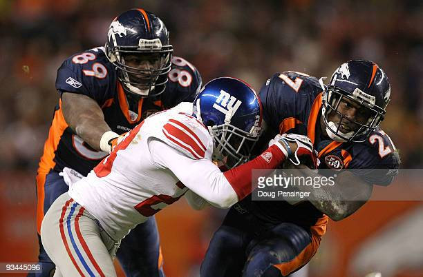 Knowshon Moreno of the Denver Broncos rushes for a first down before being tackled by Corey Webster of the New York Giants as Daniel Graham of the...