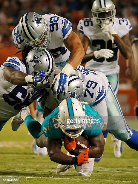 Knowshon Moreno of the Miami Dolphins is brought down by a host of Dallas Cowboys defenders including Stephen Goodin in the second quarter during a...