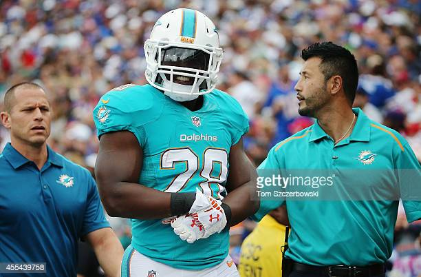 Knowshon Moreno of the Miami Dolphins is walked off the field after being injured against the Buffalo Bills during the first half at Ralph Wilson...