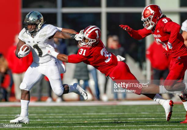 J Knox of the Purdue Boilermakers runs the ball and stiff arms defender Bryant Fitzgerald of the Indiana Hoosiers at Memorial Stadium on November 24...