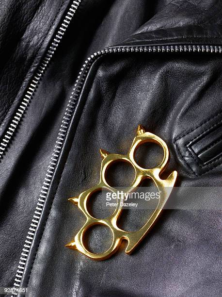 Knuckle duster lying on leather jacket.