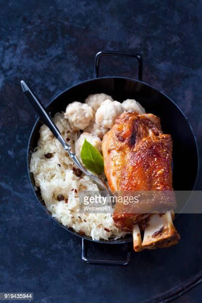 knuckle of pork with bread dumplings and sauerkraut in roasting tray - zuurkool stockfoto's en -beelden