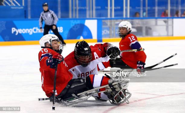 Knut Andre Nordstoga of Norway battles for the puck with Kazuhiro Takahashi of Japan in the Ice Hockey Classification game between Norway and Japan...