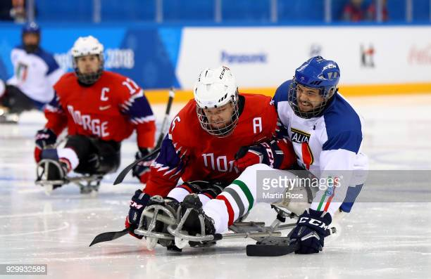 Knut Andre Nordstoga of Norway battles for the puck with Sandro Kalegaris of Italy in the Ice Hockey Preliminary Round Group A game between Norway...