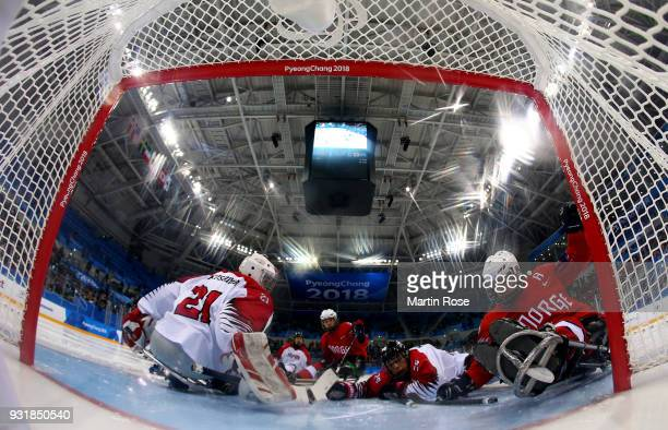 Knut Andre Nordstoga of Norway scores a goal over Shinobu Fukushima goaltender of Japan in the Ice Hockey Classification game between Norway and...