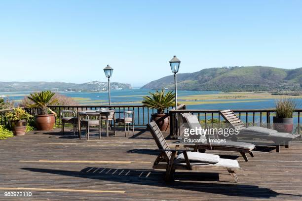 Knysna Lagoon Western Cape South Africa Table and chairs and sun loungers on wooden decking overlook the Lagoon