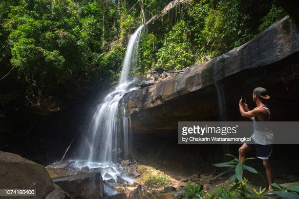 ko kut (koh kood) island - a man standing below the rocky cliff taking photograph of huang nam keaw waterfall by his smart phone. - local landmark stock pictures, royalty-free photos & images