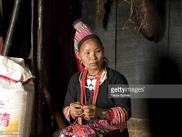 A Ko Loma ethnic minority woman sews traditional clothing in her home Ban Lao Leo Phongsaly province Lao PDR One of the most ethnically diverse...