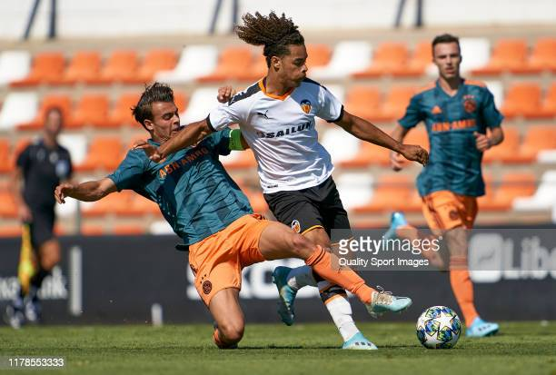 Koba Koindredi of Valencia is tackled by Enric Llansana of Ajax during the UEFA Youth League match between Valencia CF and AFC Ajax at Estadio...