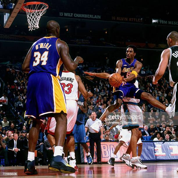 Kobe Bryan of the Western Conference All-Stars makes a pass to teammate Shaquille O'Neal against Alonzo Mourning of the Eastern Conference All-Stars...