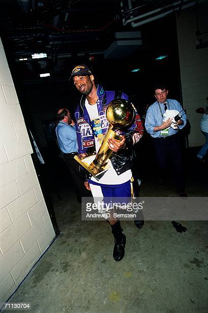 Kobe Bryant 38 of the Los Angeles Lakers walking with the NBA Championship trophy after defeating the Philadelphia 76ers in game five of the 2001 NBA...