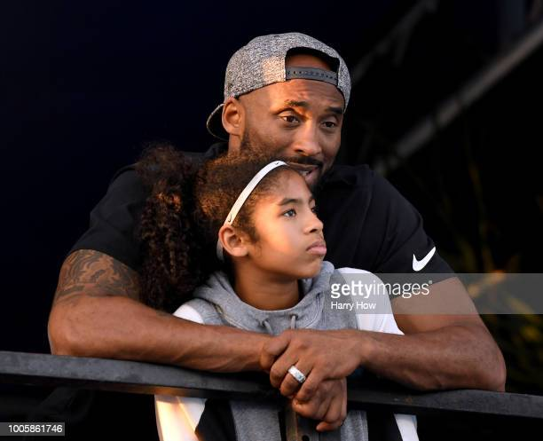 Kobe Bryant and daughter Gianna Bryant watch during day 2 of the Phillips 66 National Swimming Championships at the Woollett Aquatics Center on July...