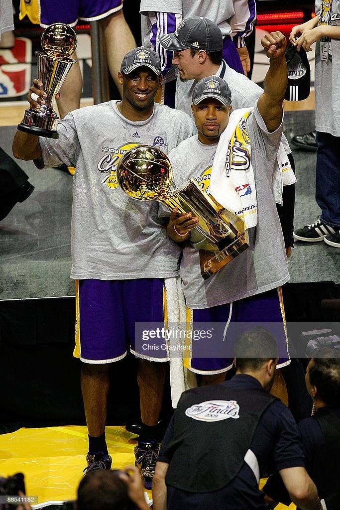 Kobe Bryant #24 and Derek Fisher #2 of the Los Angeles Lakers celebrate after the Lakers' defeated the Orlando Magic in Game Five of the 2009 NBA Finals on June 14, 2009 at Amway Arena in Orlando, Florida. The Lakers won 99-86.