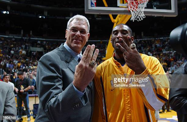 Kobe Bryant and head coach Phil Jackson of the Los Angeles Lakers show off their new championship rings before the NBA season opener against the San...