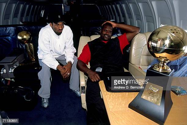 Kobe Bryant and Shaquille O'Neal of the Los Angeles Lakers chat on board the Lakers' team flight back to Los Angeles the day after defeating the...