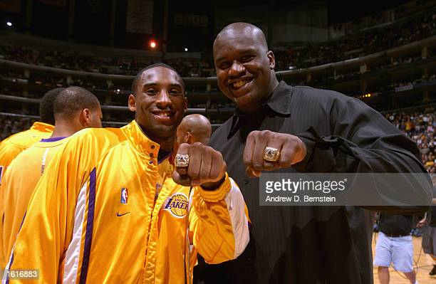 Kobe Bryant and Shaquille O'Neal of the Los Angeles Lakers show off their NBA Championship rings prior to the season opener against the San Antonio...