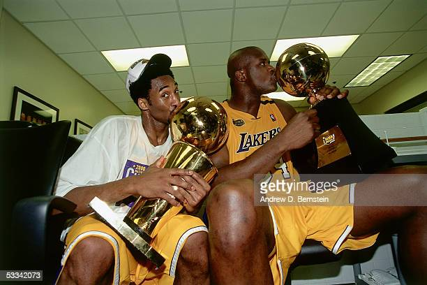 Kobe Bryant and Shaquille O'Neal of the Los Angeles Lakers sit with the NBA Championship Trophy and the Playoff MVP Trophy after winning the 2000 NBA...