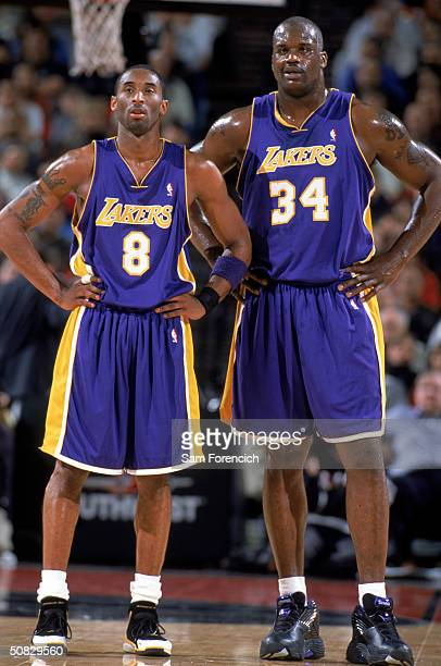 Kobe Bryant and Shaquille O'Neal of the Los Angeles Lakers stand side by side as they wait for play during the game against the Portland Trail...