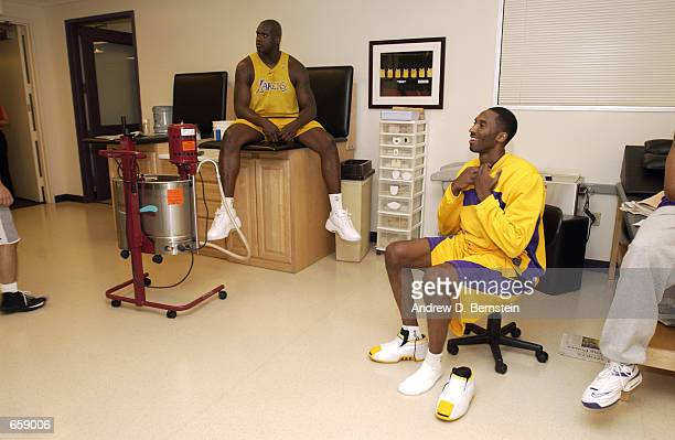 Kobe Bryant and Shaquille O'Neal of the Los Angeles Lakers take a break in the locker room at the Lakers practice facility on June 6 2002 in Los...