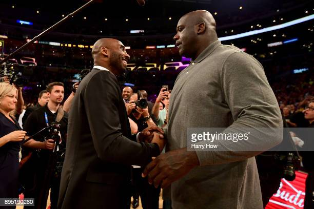 Kobe Bryant and Shaquille O'Neal shake hands at halftime after both of Bryant's and Los Angeles Lakers jerseys are retired at Staples Center on...