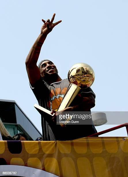 Kobe Bryant holds the Larry O'Brien trophy and waves to the crowd from the top of a double decker bus at the start of the Los Angeles Lakers NBA...