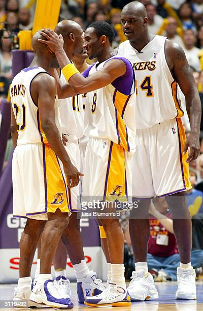 Kobe Bryant jokes with Gary Payton of the Los Angeles Lakers as teammates Shaquille O'Neal and Karl Malone talk behind them during the game against...