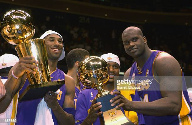 Kobe Bryant Lindsey Hunter and Shaquille O'Neal of the Los Angeles Lakers hold their 2002 NBA Championship Trophies after Game four of the 2002 NBA...