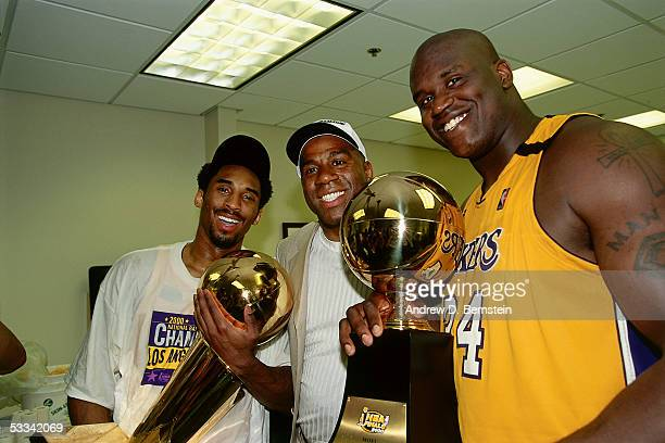 Kobe Bryant Magic Johnson and Shaquille O'Neal of the Los Angeles Lakers pose for a photo with the NBA Championship Trophy and the Playoff MVP Trophy...