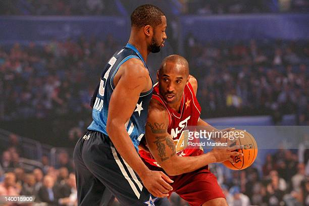 Kobe Bryant of the Los Angeles Lakers and the Western Conference looks to move the ball against Dwyane Wade of the Miami Heat and and the Eastern...