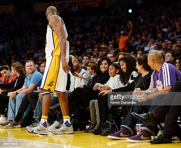 Kobe Bryant of the Los Angeles Lakers asks for a high five from his daughters Natalia and Gianna as wife Vanessa looks on during the basketball game...