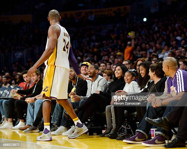 Kobe Bryant of the Los Angeles Lakers asks for a high five from his youngest daughters Gianna as sister Natalia and wife Vanessa looks on during the...