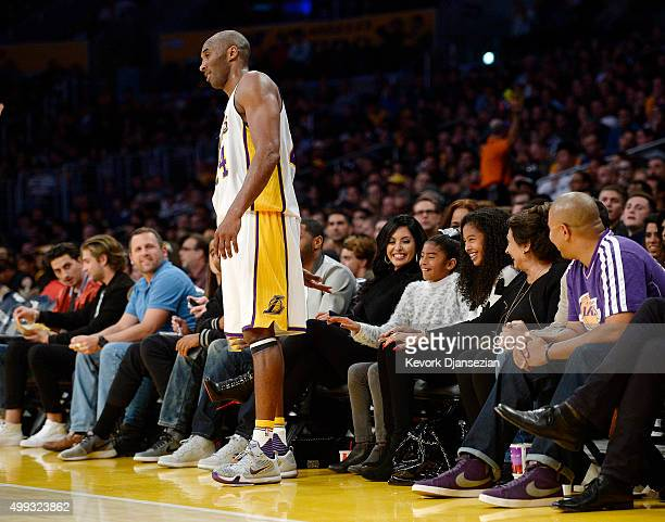 Kobe Bryant of the Los Angeles Lakers asks for a low five from his youngest daughters Gianna as sister Natalia and wife Vanessa looks on during the...