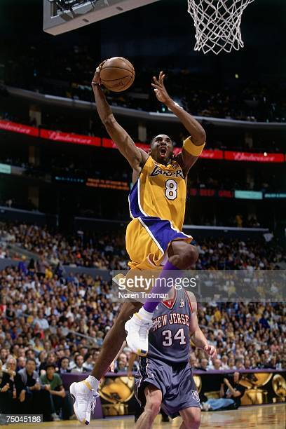 Kobe Bryant of the Los Angeles Lakers attempts a dunk against Aaron Williams of the New Jersey Nets during a 2001 NBA game at the Staples Center in...