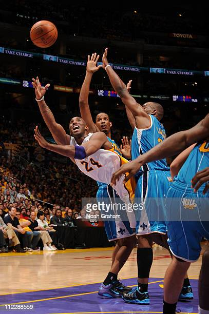 Kobe Bryant of the Los Angeles Lakers attempts a shot against Trevor Ariza and Carl Landry of the New Orleans Hornets in Game One of the Western...
